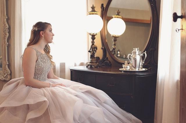 Dívka v nadýchaných šatech sedící před zrcadlem
