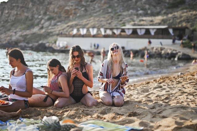 Skupina dívek sedících na pláži s mobily v rukou