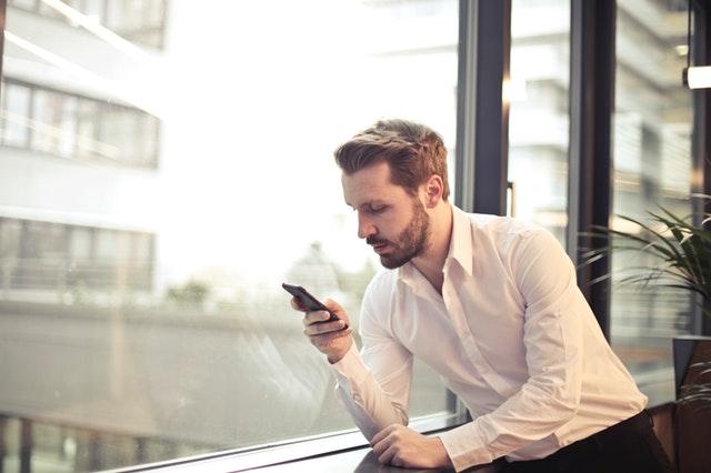 Muž, hledící do mobilu