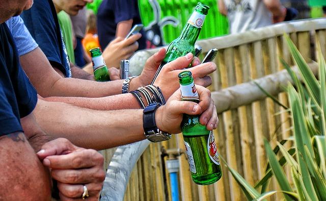 muži drží v rukou lahve piva