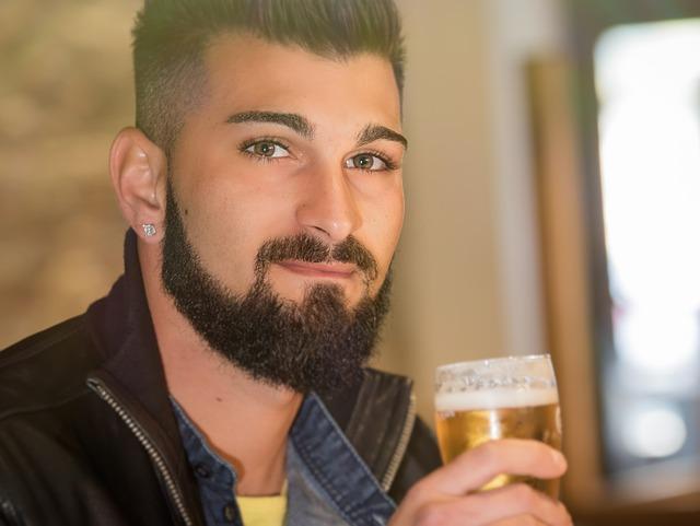 mladý muž v detailu se sklenicí piva